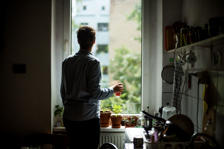 Rear view of person looking out kitchen window