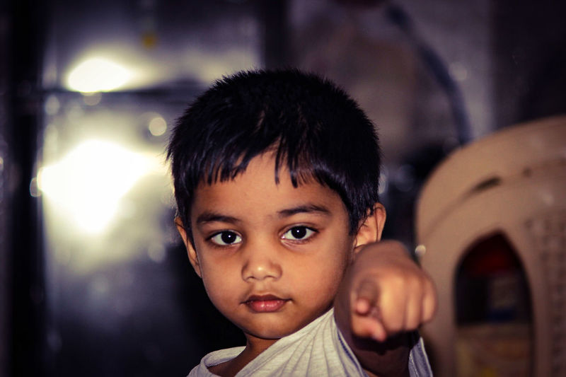Portrait of cute boy pointing while at home