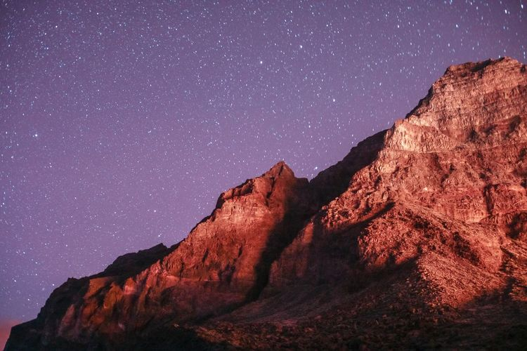 Rock formation against sky at night
