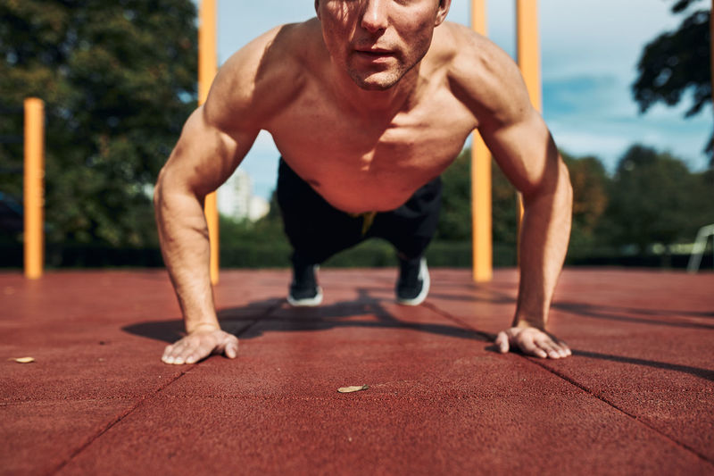 Young shirtless man bodybuilder doing push-ups on a red rubber ground during his workout