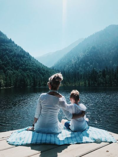 Rear view of mother and son with arm around sitting by lake against mountain