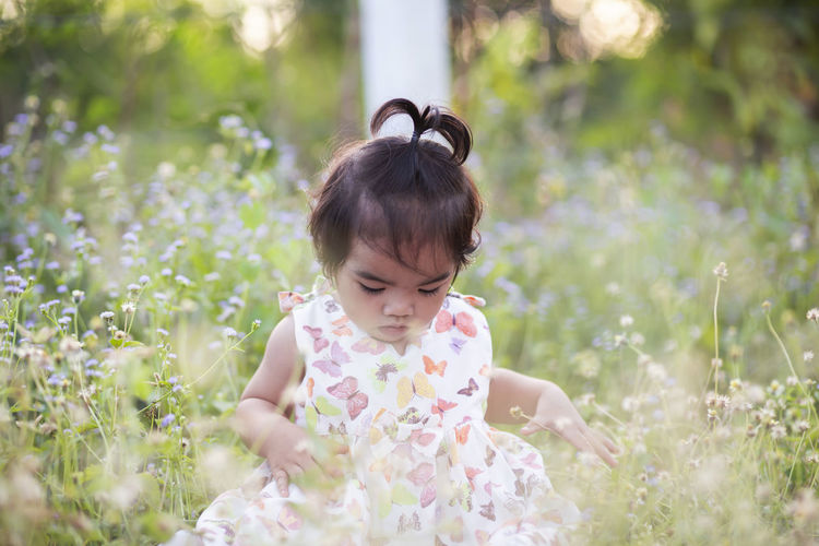 Cute girl with flowers on field