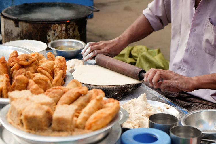 Cropped hand rolling dough at food stall