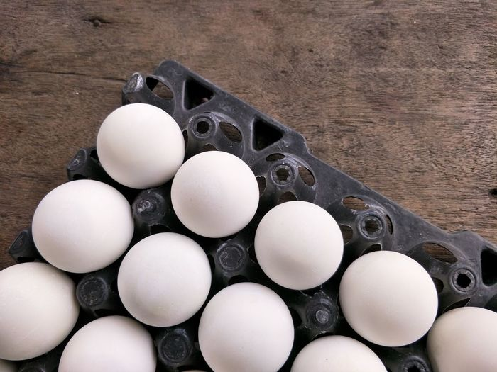 High angle view of eggs in carton on wooden table