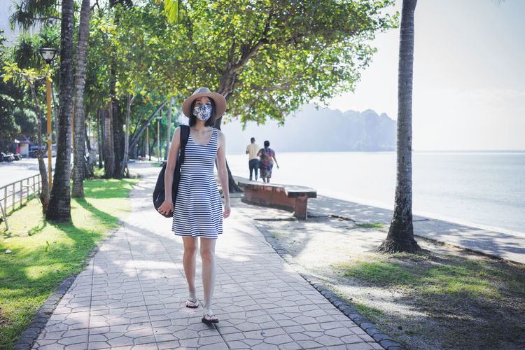 Full length of woman standing on footpath by trees