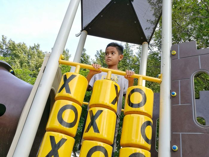 Low Angel View Of Boy Standing On Play Equipment At Playground