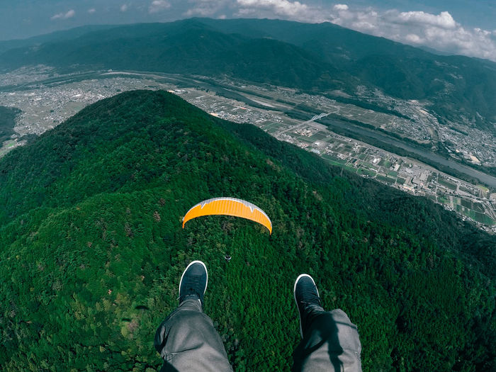 Low Section Of Person Paragliding Above Mountain Against Sky