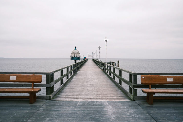 Empty pier over sea against sky