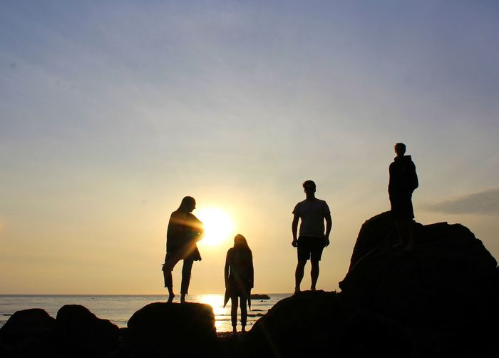 Silhouette people on rock at beach against sky during sunset