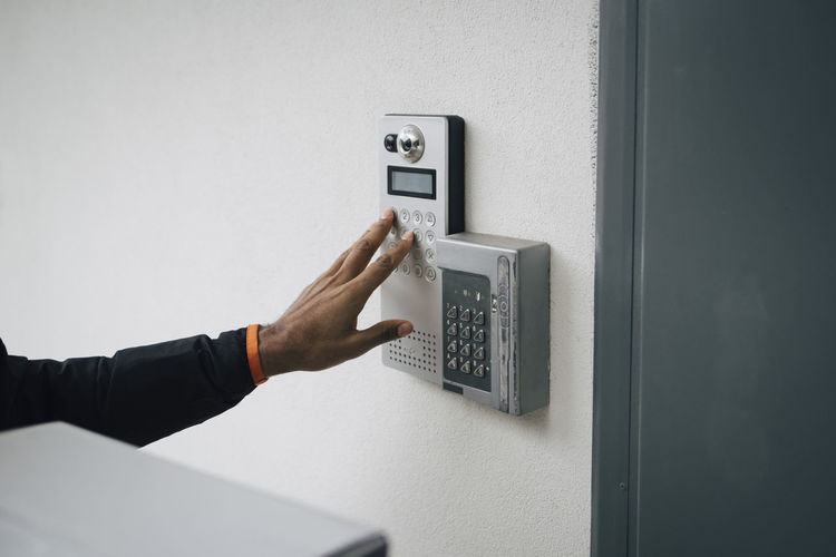 Close-up of hand holding camera against wall