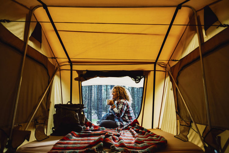 Smiling woman sitting against trees seen through tent