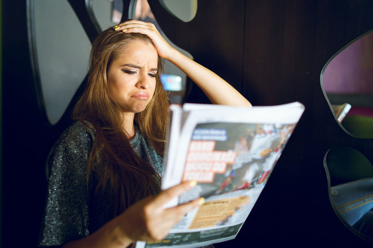 Sad young woman reading magazine at home