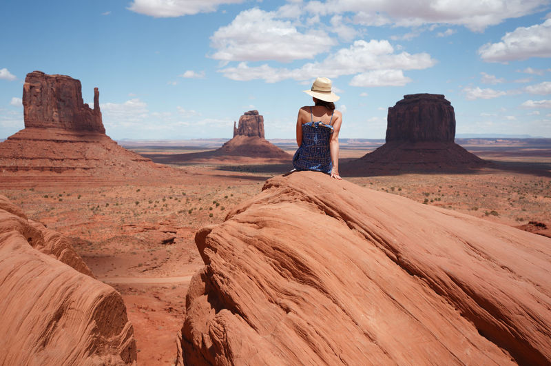 Rear View Of Woman Sitting On Rock Formation In Desert Against Landscape