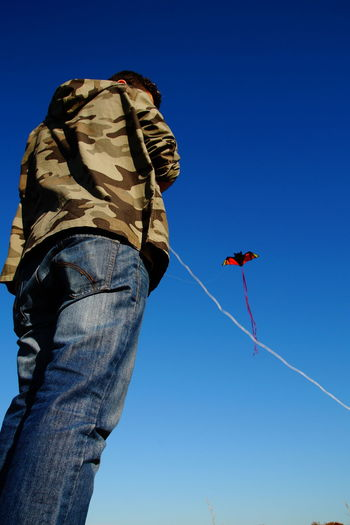 Low angle view of man flying kite against clear blue sky