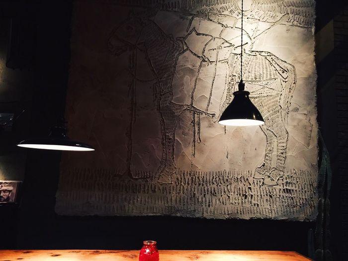 Illuminated lamp on wall of building