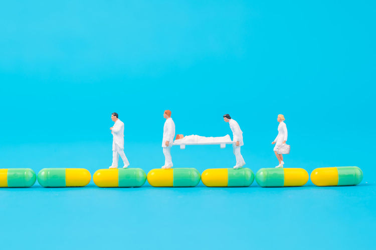 miniature people healthy team and medical drug,medical concept Doctor  Drug Hospital Medicine PainKiller Teamwork Therapy Antibiotic Blue Background Capsule Figurine  Healthcare And Medicine Miniature People Patient Pill Small Treat