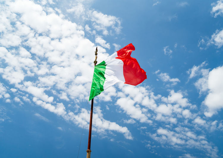 Low angle view of italian flag against blue sky