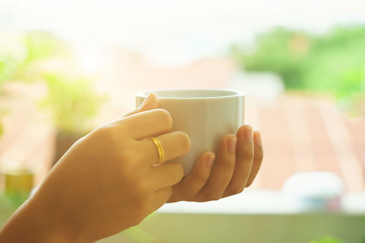 Morning coffee concept. People holding a cup of coffee drinks in the morning after wake-up. Adult Close-up Coffee Coffee - Drink Coffee Cup Cup Day Drink Drinking Finger Focus On Foreground Food And Drink Glass Hand Holding Hot Drink Human Body Part Human Hand Latte Mug Nail One Person Refreshment Tea Cup Women