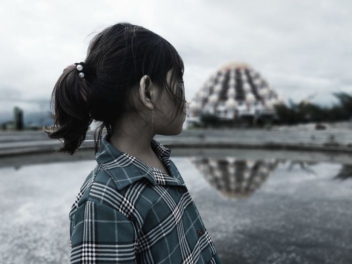 Portrait of young woman looking at mosque 99 dooms in makassar city