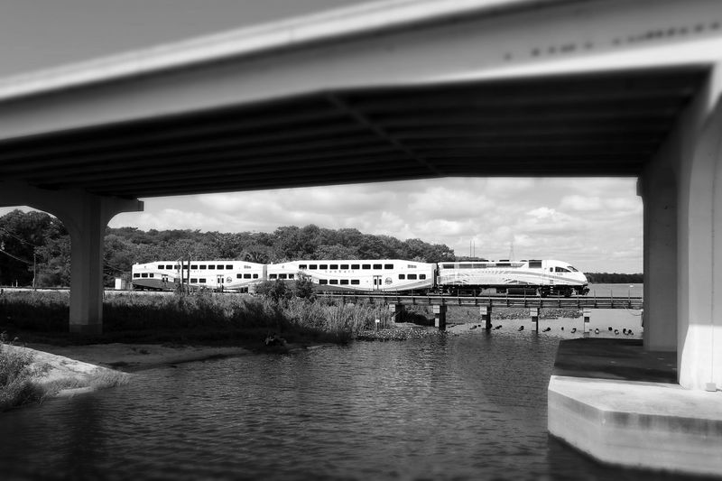Riverside Waterfront Under The Freeway  Overpass Architecture Built Structure Railway Bridge Train Sunrail Man Fishing Trees Sky And Clouds From A Distance Monochrome Black And White Blurred Tiltshift Photography