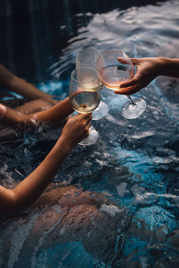 Ladies women friends with wine glasses cheers hot tub summer
