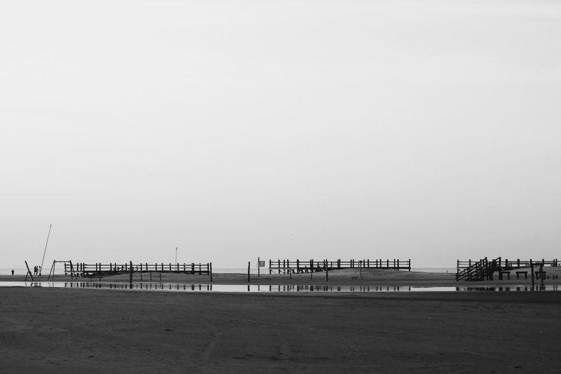 Pier on beach against clear sky