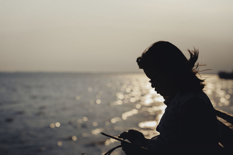 Woman using mobile phone at beach against sky