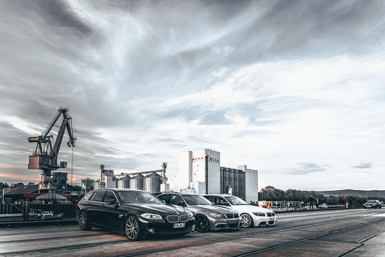 Vehicles on road against sky in city