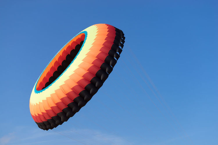 Low angle view of hot air balloons against clear blue sky
