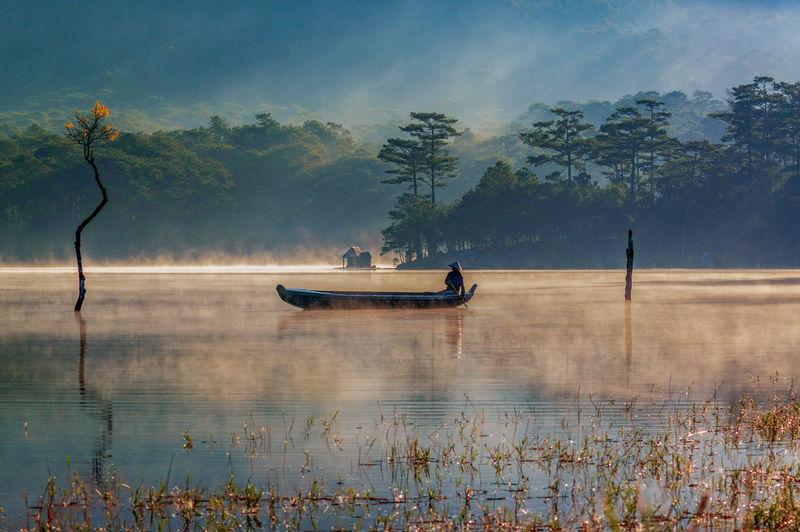 Man in rowboat on lake at sunset
