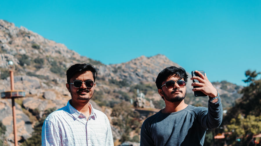Friends taking selfie on smart phone against mountain