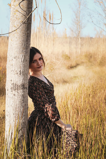 Young woman on tree trunk in field