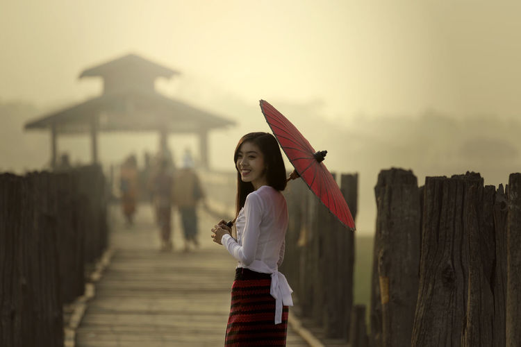 Young woman with umbrella standing on pier against sky