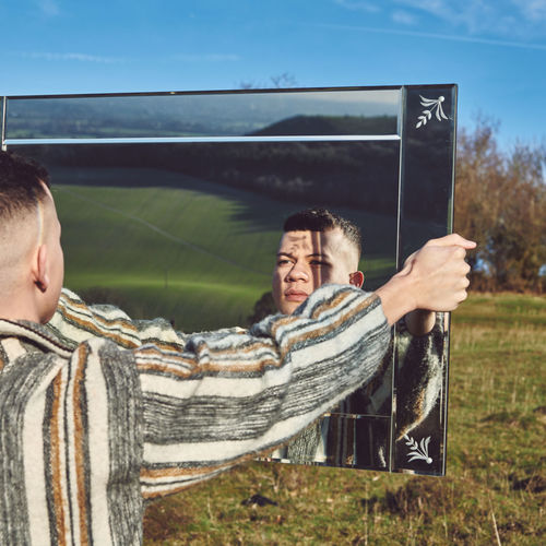 Young man holding mirror on field