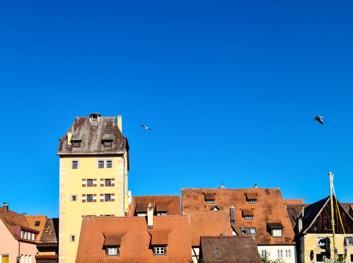 View of buildings against clear blue sky