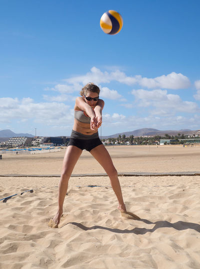 Woman playing volleyball at beach against sky