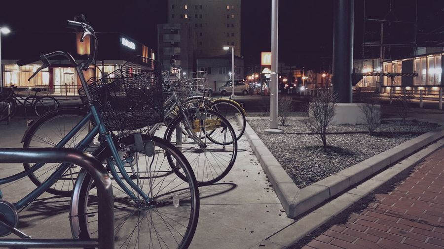 Bicycle parked on sidewalk by building at night
