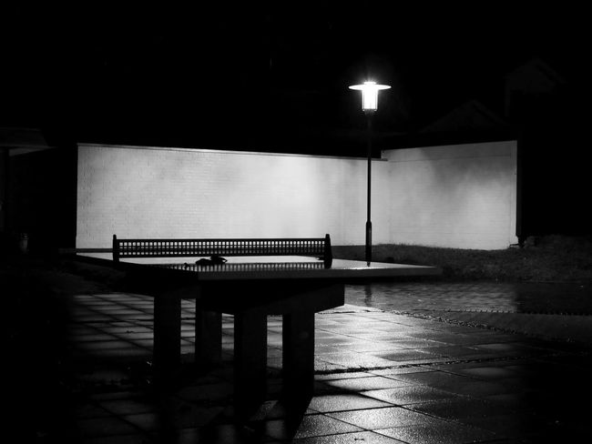 Black And White Empty Illuminated Lamp Light Light And Shadow Monochrome Photography Night No People Outdoors Overnight Success Shiny Tabletennis Wet Taking Photos From My Point Of View Electric Light Wall Brick Wall Selective Focus Perspective Built Structure