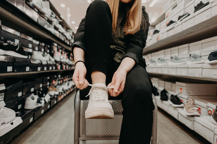 Midsection of woman tying shoelace in store
