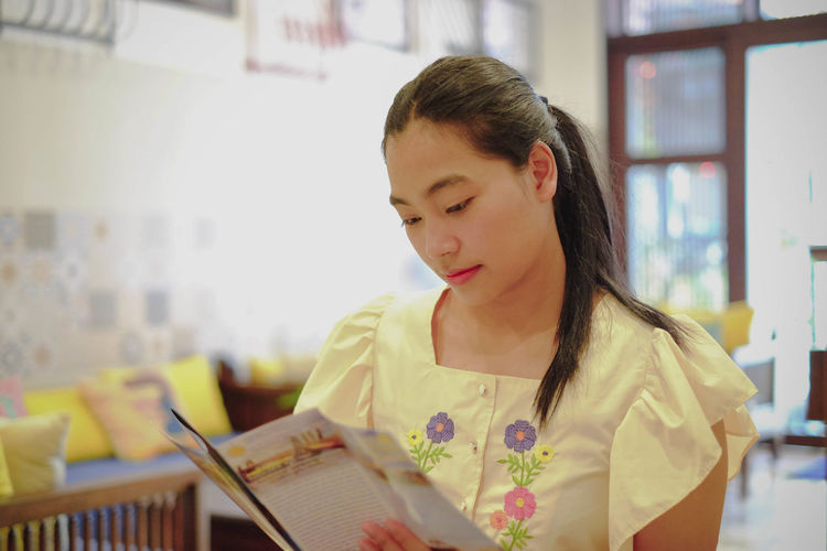Portrait of young woman looking at book