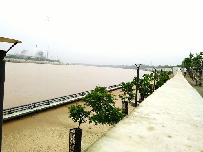 Riverfront, Ahmedabad,India Riverfront River View Riverside Outdoors Day Water People Walking  City Scenics Plants On The Wall Jogging Time Jogging Path Tree Nature Beauty In Nature Sky Industrial Building  Power Station Cloudy Sky 💙 Industrial Art Connected By Travel