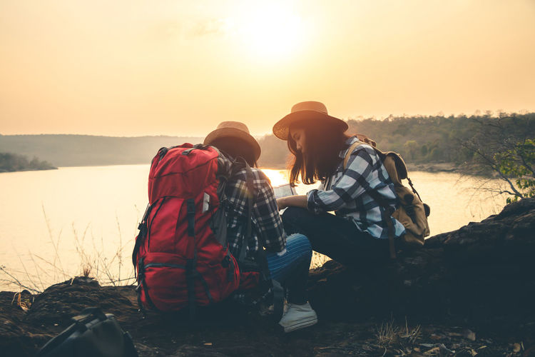 Lifestyles Nature People Outdoors Landscape Backpack Backpacking Backpacker Travel Map Women Sky Sunlight Two People Sunset Water Young Men Positive Emotion Young Adult Togetherness Leisure Activity Bonding