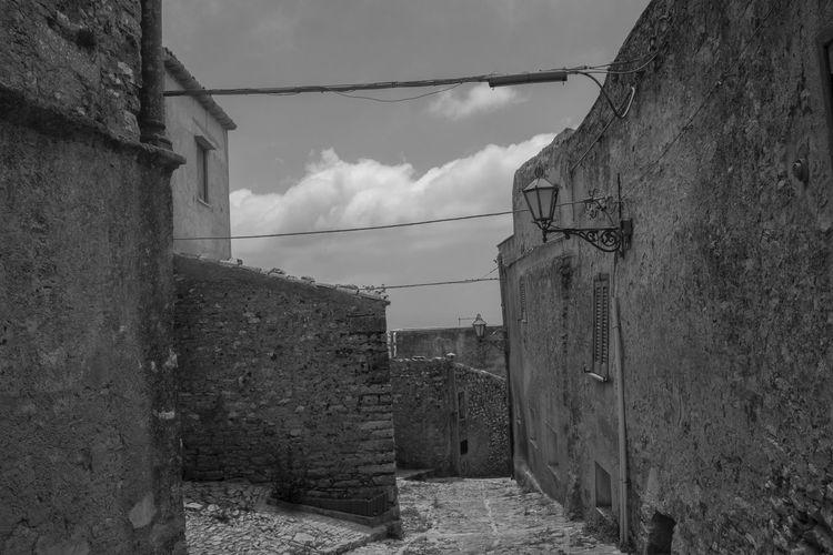 Alley amidst buildings against sky