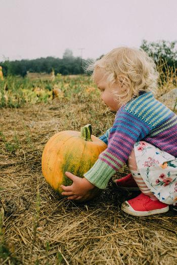 Boy holding pumpkin on field