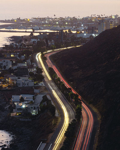 High angle view of light trails on road amidst buildings in city