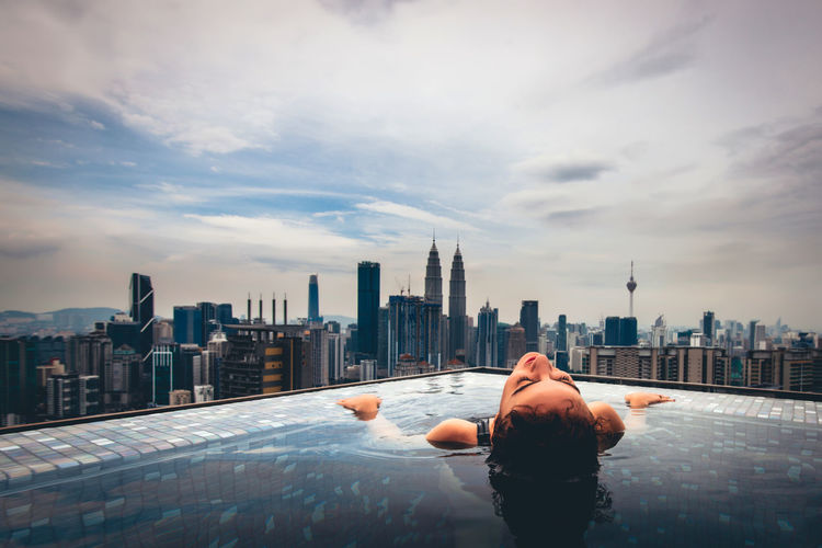 Man and woman in swimming pool against buildings in city