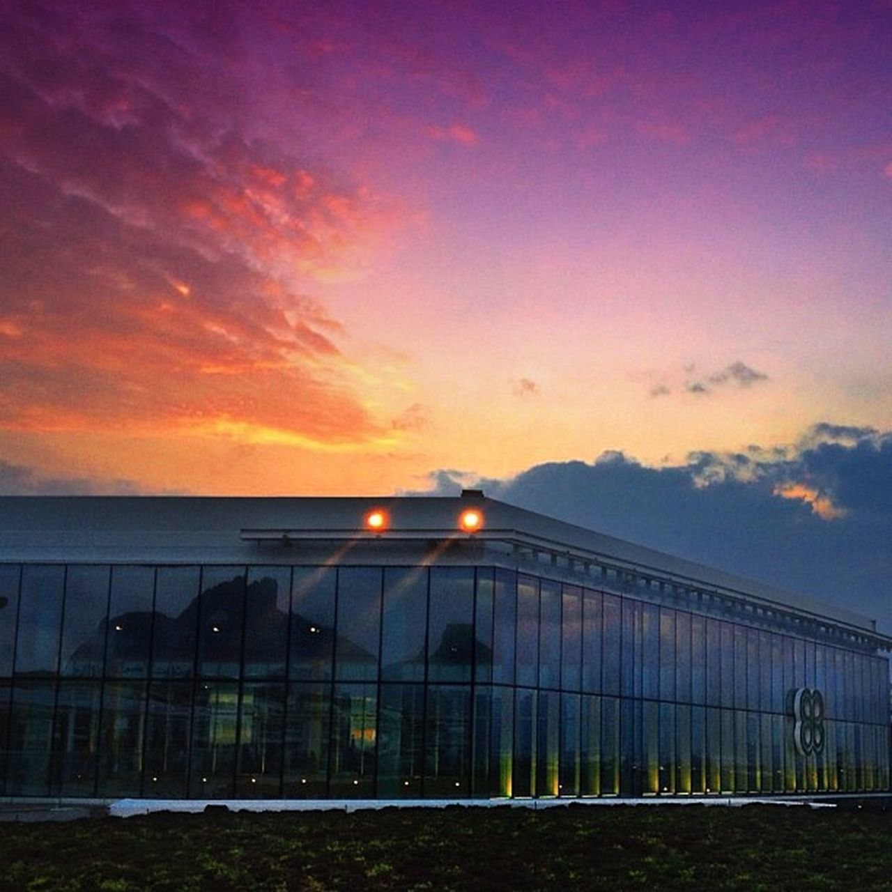 sky, architecture, built structure, building exterior, sunset, outdoors, no people, cloud - sky, illuminated, grass, nature, day