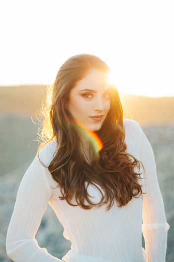 Portrait of beautiful woman standing against sky during sunset