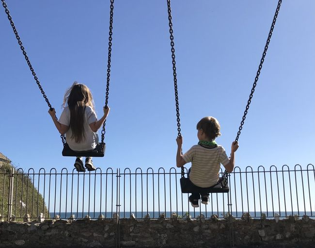 Rear view of children sitting on swing at playground