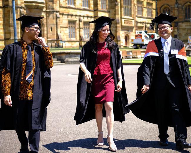People In Graduation Gown Walking On Street